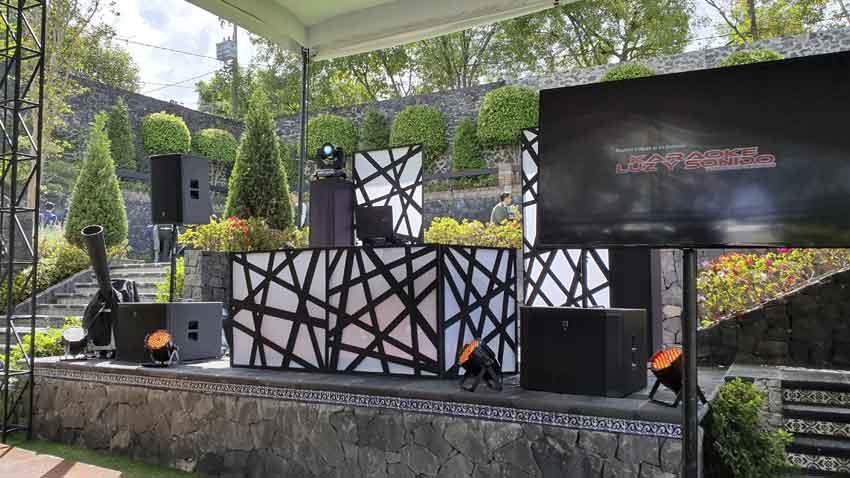 dj para fiestas KLS cabina de dj en color blanco y negro delante pantalla con logotipo Karaoke Luz y Sonido