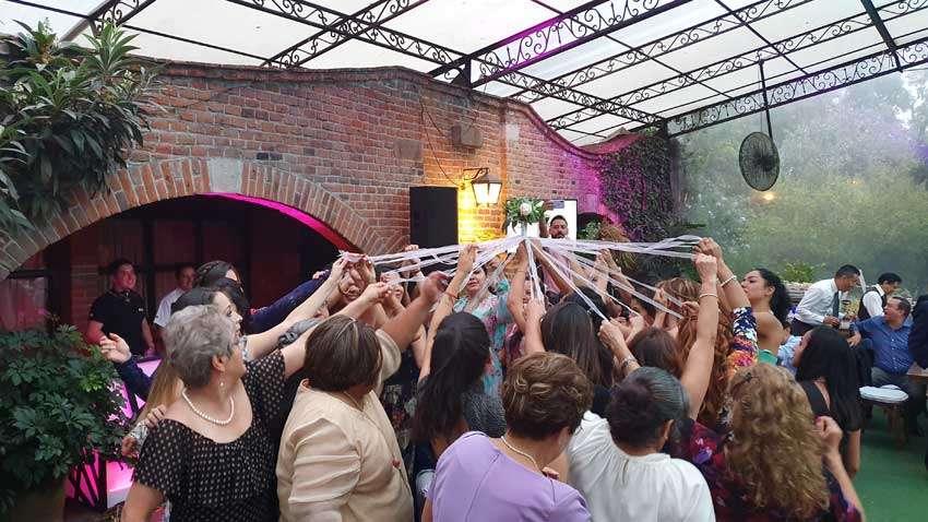 fiesta con dj KLS gente realizando dinámica de ramo durante una boda en jardín Maja