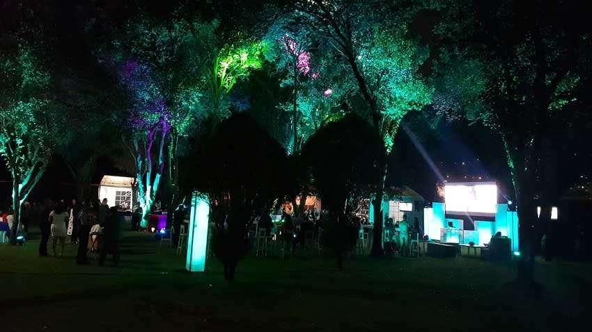 fiesta con dj KLS vista lejana a evento en jardín con iluminación en colores verdes destacando en el follaje de los arboles