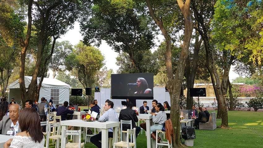 fiesta con dj KLS gente sentada en mobiliario lounge disfrutando de la música proyectada en pantalla