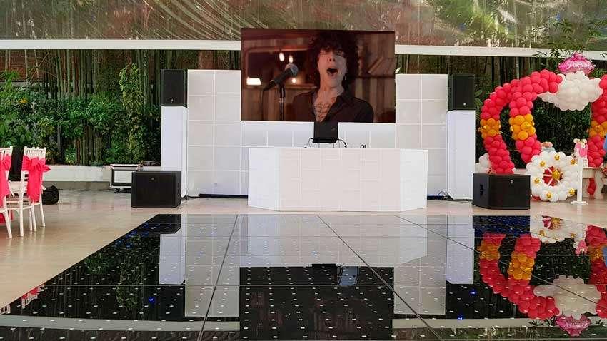 fiesta con dj KLS montaje de pantalla de leds con pista iluminada al frente mampara en blanco
