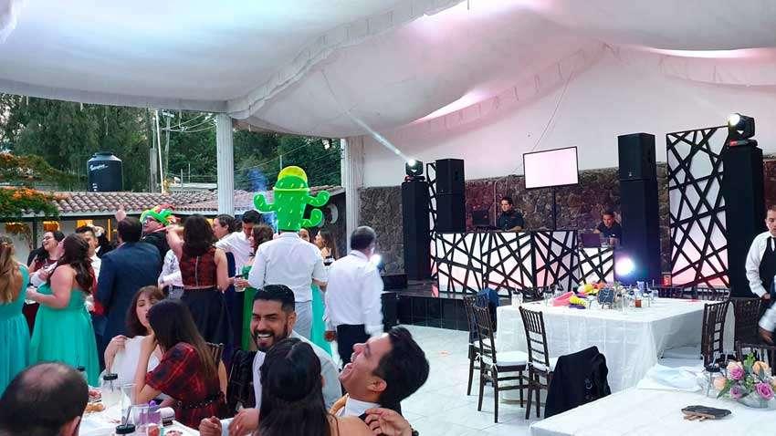 fiesta con dj KLS gente sonriendo y bailando con sombreros de hule espuma dj con mampara en blanco y negro