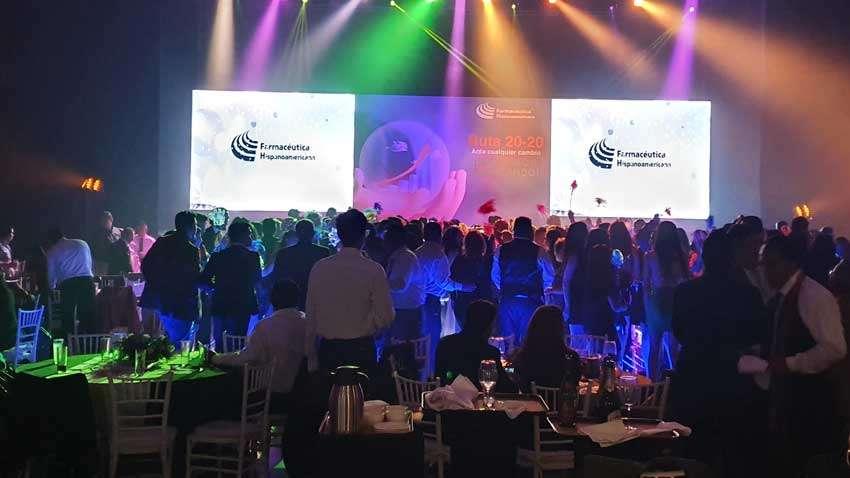 fiesta con dj KLS gente bailando, al frente dos pantallas led iluminado en colores