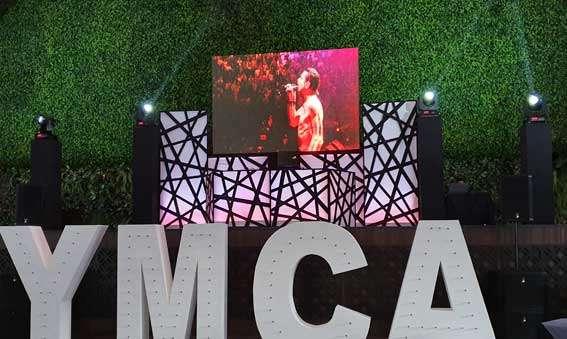 dj para eventos KLS Equipo PREMIERE Cabina de dj color negro y blanco con pantalla led arriba de escenario adornado con letras YMCA