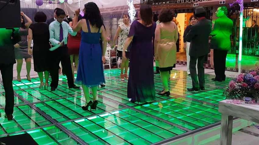 dj para fiesta KLS pista de cristal iluminada en verde con gente arriba bailando